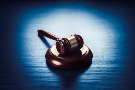 juridical: high contrast image of Judge gavel on a blue wooden background