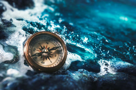 high contrast image of a compass on rocks