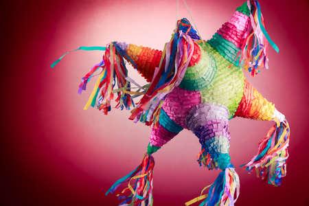 赤の背景に誕生日で使用されるカラフルなメキシコのピニャータ 写真素材