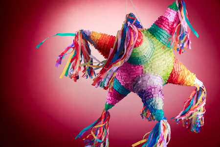 Colorful mexican pinata used in birthdays on red background Stockfoto