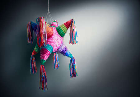 pinata: Colorful mexican pinata used in birthdays on a grey background Stock Photo