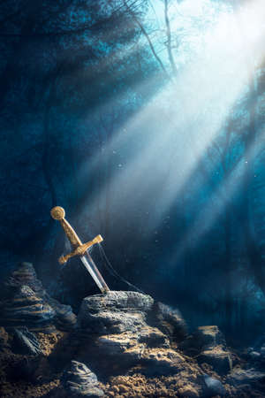 arthur: High contrast image of Excalibur, sword in the stone with light rays and dust specs in a dark forest