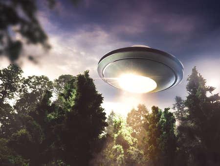 UFO zweeft boven een bos in de schemering Stockfoto