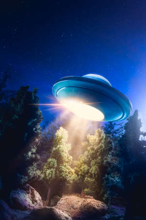 lightbeam: UFO hovering over a forest at night Stock Photo