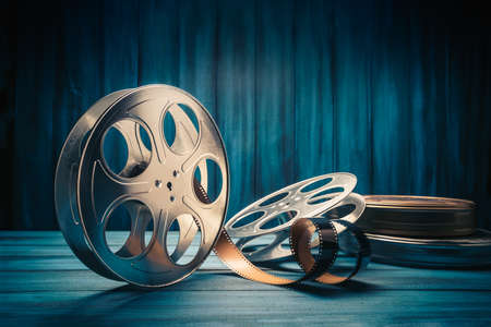 35 mm film reels and cans with dramatic lighting on a wooden background Stock Photo