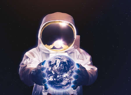 Astronaut holding the earth on his hands (Elements of this image were furnished by NASA) Zdjęcie Seryjne - 75329478