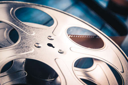 35 mm film reel with dramatic lighting on a wooden background