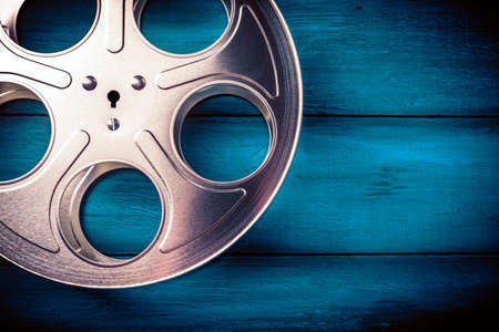 35mm film reel with dramatic lighting on a wooden background