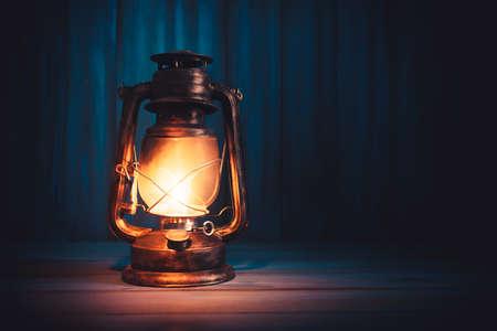 Kerosene lamp or lantern on a wooden background with dramatic lighting