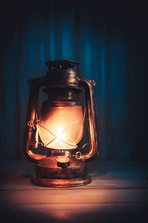 antique: Kerosene lamp or lantern on a wooden background with dramatic lighting