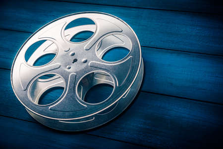 lighting background: 35mm film reel with dramatic lighting on a wooden background