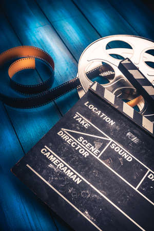 traditional: 35mm film, reel and movie clapper with dramatic lighting on a wooden background