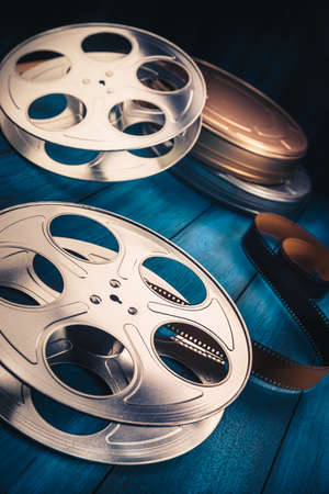 antique: 35 mm film reels and cans with dramatic lighting on a wooden background Stock Photo