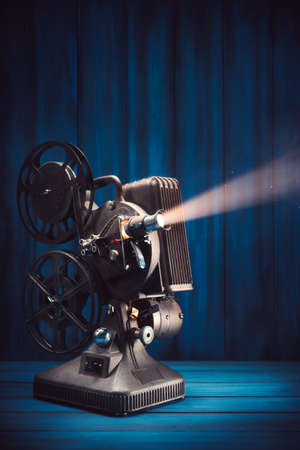 filmmaker: film projector on a wooden background with dramatic lighting and selective focus Stock Photo
