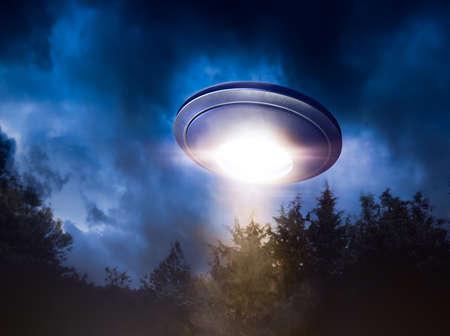 Low key beeld van UFO zweven over een bos in de nacht