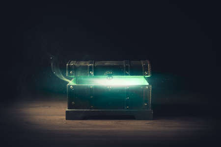 open pandoras box with green smoke on a wooden background high contrast image Imagens
