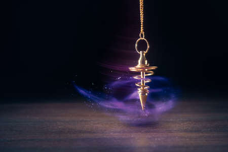 Pendulum used for hypnotism and readings swinging with motion blur Banco de Imagens - 75329519