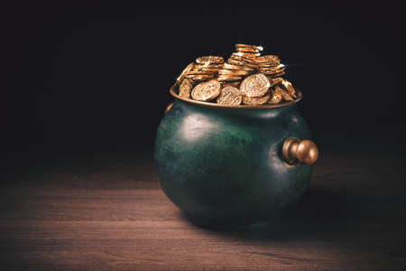 gold coins in a green pot on a dark background Archivio Fotografico