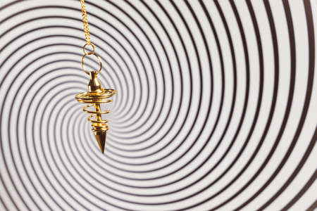 Pendulum used for hypnotism and readings on a swirl background Stock Photo - 75329527