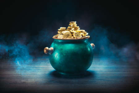 gold coins in a green pot on a dark background Stock Photo