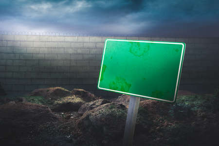 protectionism: border concept with blank sign in front of a high wall and dramatic lighting
