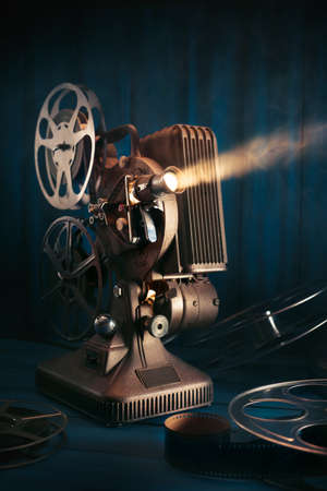 film making scene with old 8mm movie projector with 35mm reels and film on a wooden background with dramatic lighting Stock Photo