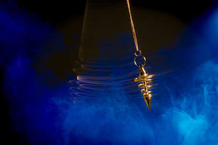 Pendulum used for hypnotism and readings swinging with motion blur