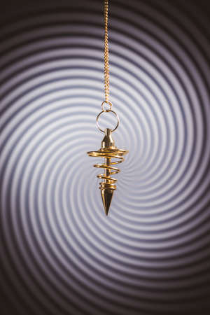 Pendulum used for hypnotism and readings on a swirl background
