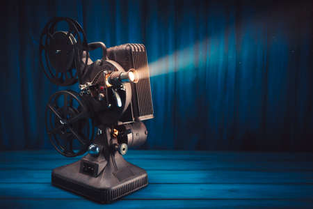 film projector on a wooden background with dramatic lighting and selective focus Stok Fotoğraf