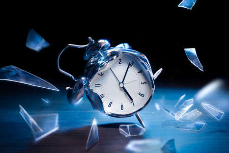 wood floor: Busted alarm clock with broken glass on a dark background