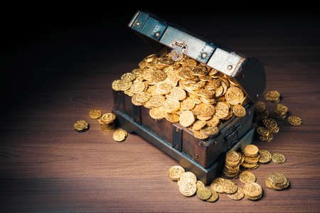 Open treasure chest filled with gold coins  HIgh contrast image Stock Photo