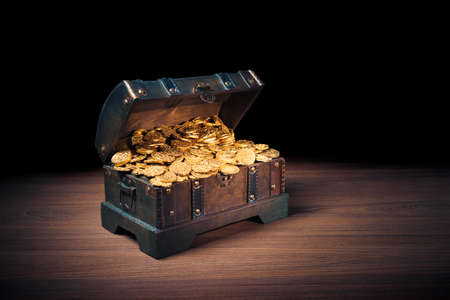 golden: Open treasure chest filled with gold coins  HIgh contrast image Stock Photo