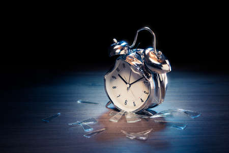 Busted alarm clock with broken glass on a dark background