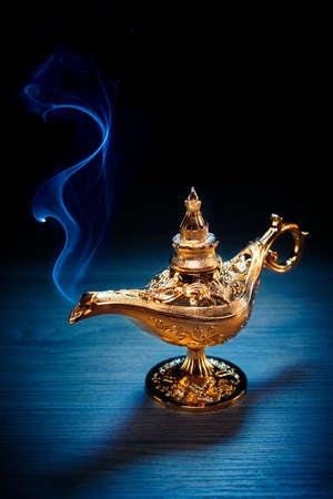 Mágica lámpara de genio con humo sobre un fondo oscuro