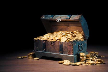 Otwarty skarb wypełniony złotymi monetami / kontrast obrazu HIgh