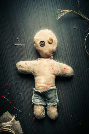 pierce: Voodoo Doll on a wooden background with dramatic lighting Stock Photo