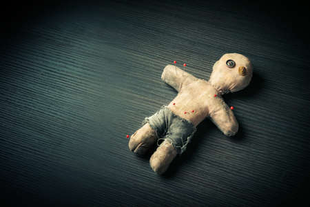 Voodoo Doll on a wooden background with dramatic lighting Reklamní fotografie