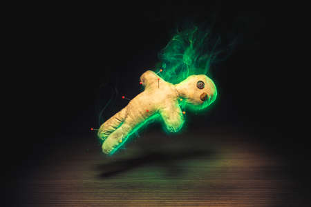 Voodoo Doll on a wooden background with dramatic lighting Stock Photo