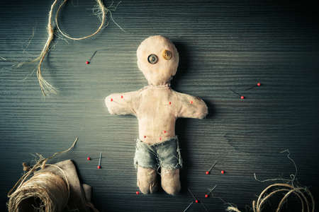 vodoo: Voodoo Doll on a wooden background with dramatic lighting Stock Photo