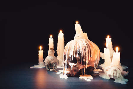Creepy image of skull with a melting candle on top high contrast image