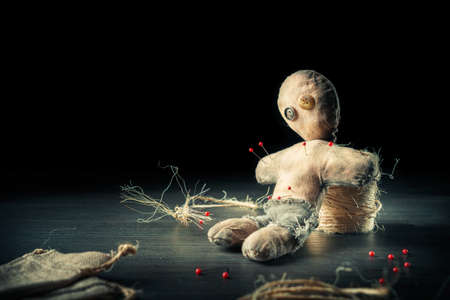 curse: Voodoo Doll on a wooden background with dramatic lighting Stock Photo