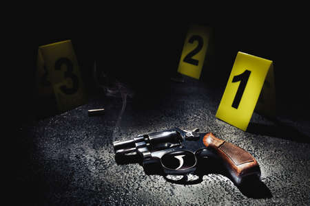 gun with smoke on the floor and evidence markers, high contrast image