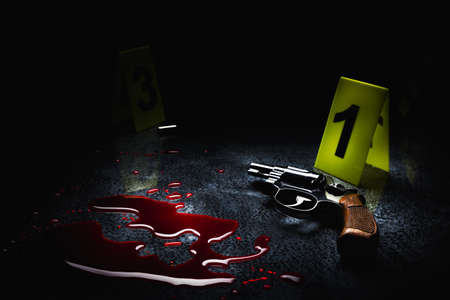 crime scene concept with a gun on a blood puddle with evidence markers on a dark background ,high contrast image Stock Photo