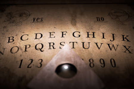 Talking board and planchette used on seances for communicating with the dead, high contrast image Stock Photo