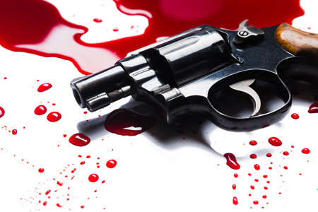 gun on a blood puddle isolated on white