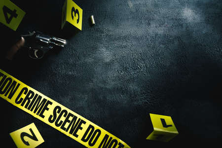 Crime scene concept with a gun and evidence markers , high contrast image Foto de archivo