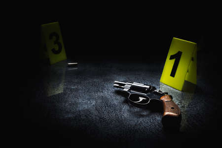 Crime scene concept with a gun and evidence markers, high contrast image Stock Photo