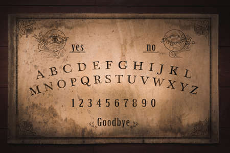 Talking board and planchette used on seances for communicating with the dead, high contrast image Фото со стока