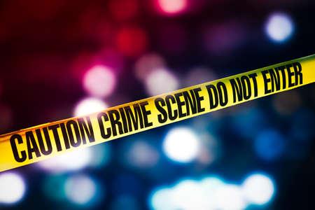 hoog contrast afbeelding van Crime scene tape met rode en blauwe lichten op de achtergrond Stockfoto