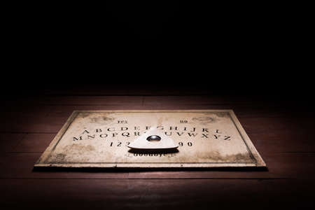 Talking board and planchette used on seances for communicating with the dead, high contrast image Archivio Fotografico